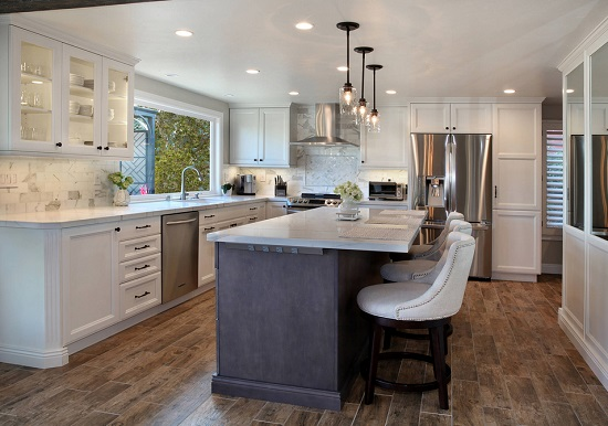 An image of a transitional kitchen. A black-on-black built-in power strip is visible along the upper edge of the cabinet.
