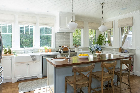A small, beachy cottage kitchen. There is a round bar sink at one corner of the kitchen island.