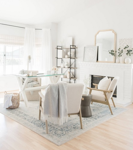 An image of a brightly lit home office laid out for meeting with clients. The white and glass desk is so minimal that at a glance the room appears more like a sitting area.