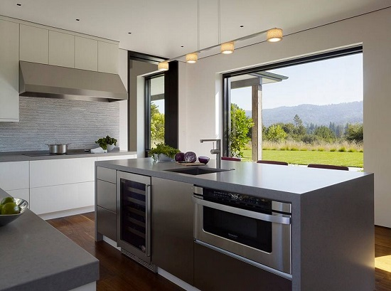 An image of a modern, slate-gray kitchen looking out on a picture window. There are a variety of appliances built into the visible face of the kitchen island
